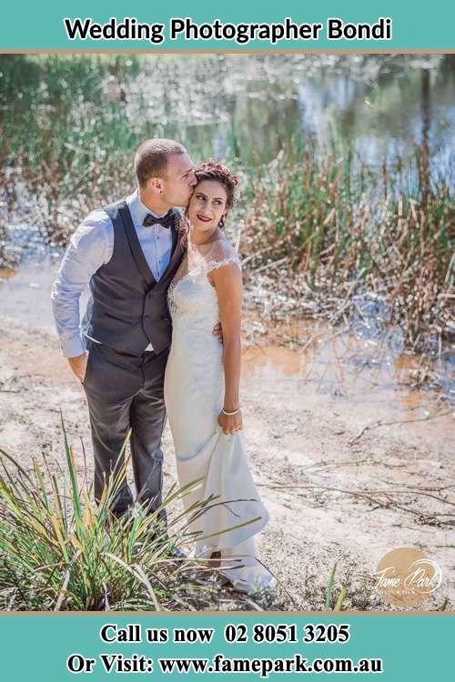 Photo of the Groom kissing his Bride near the lake Bondi NSW 2026