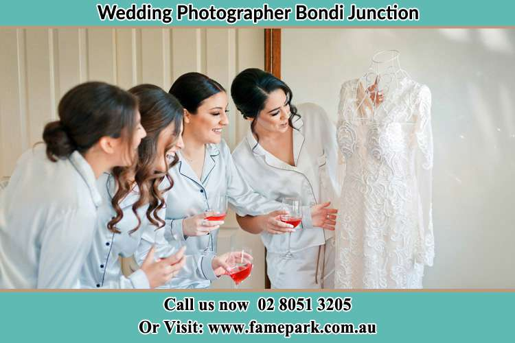 Photo of the Bride and the bridesmaid looking at the wedding gown Bondi Junction NSW 2022