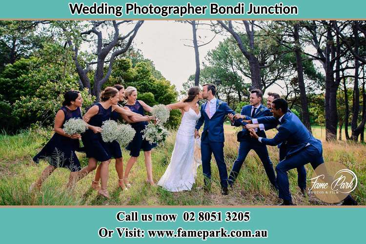 Photo of the Bride and the Groom kissing while teasing by the entourage Bondi Junction NSW 2022