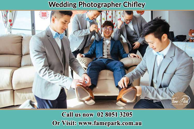 Photo of the Groom helping by the groomsmen getting ready for the wedding Chifley NSW 2036