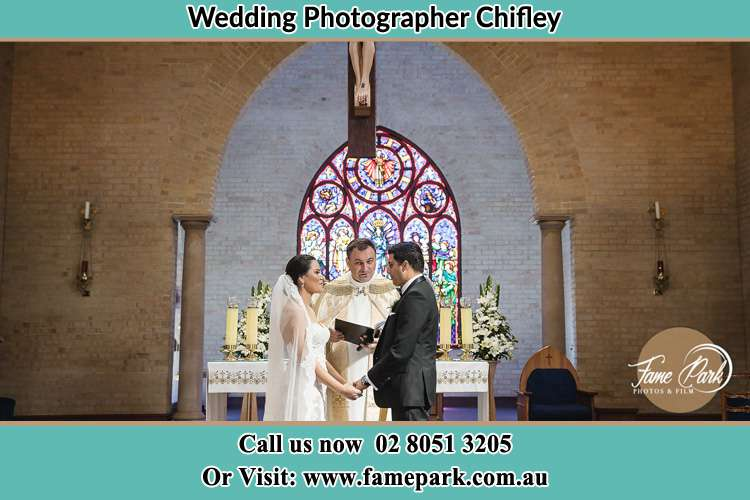 Photo of the Bride and the Groom with the Priest at the altar Chifley NSW 2036