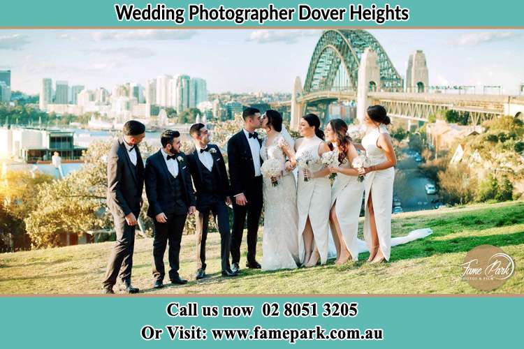 Photo of the Groom and the Bride kissing with the secondary sponsors near the bridge Dover Heights NSW 2030