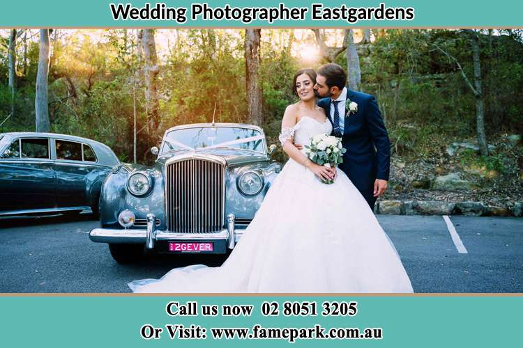 Photo of the Bride kiss by the Groom at the front of the bridal car Eastgardens NSW 2036