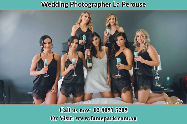 Photo of the Bride and the bridesmaids wearing lingerie holding glass of wine on the bed La Perouse NSW 2036