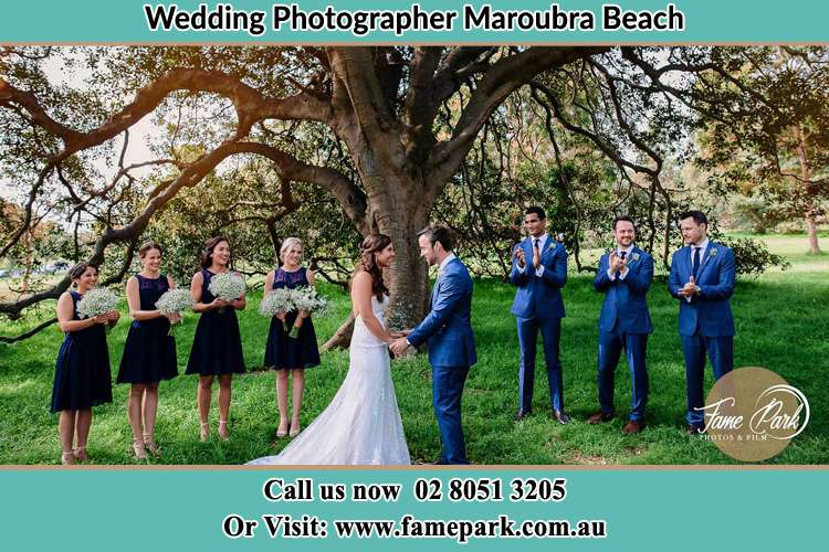 Photo of the Bride and the Groom holding hand and looking each other with the entourage Maroubra Beach NSW 2035