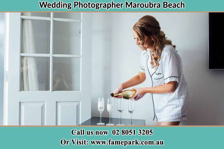 Photo of the Bride pouring wine to the glasses Maroubra Beach NSW 2035