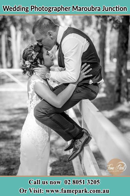 Photo of the Groom sitting on the fence kissing the Bride on the forehead Maroubra Junction NSW 2035