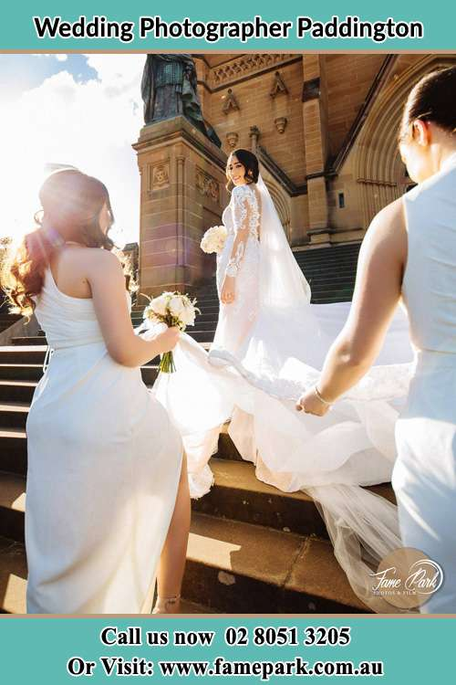 Photo of the Bride smiling to the bridesmaids holding the tail of her wedding gown in front of the church Paddington NSW 2021