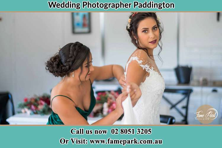 Photo of the Bride assisting by the bridesmaid fitting her wedding gown Paddington NSW 2021