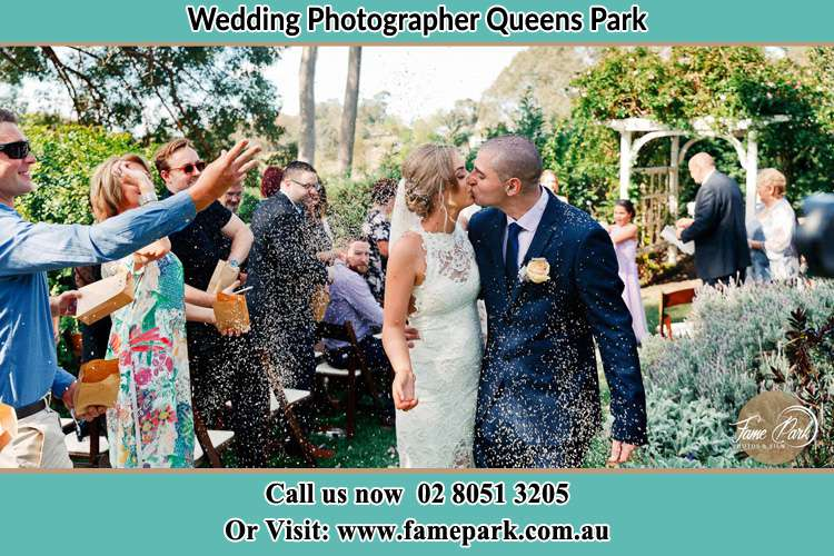 Photo of the Bride and the Groom kissing while showering rice by the visitors Queens Park NSW 2022