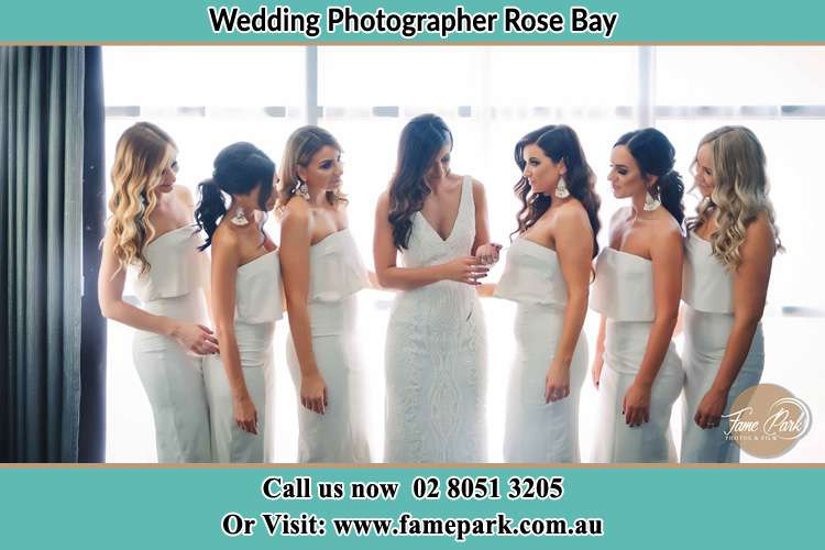 Photo of the Bride with her bridesmaids looking at her Rose Bay NSW 2029