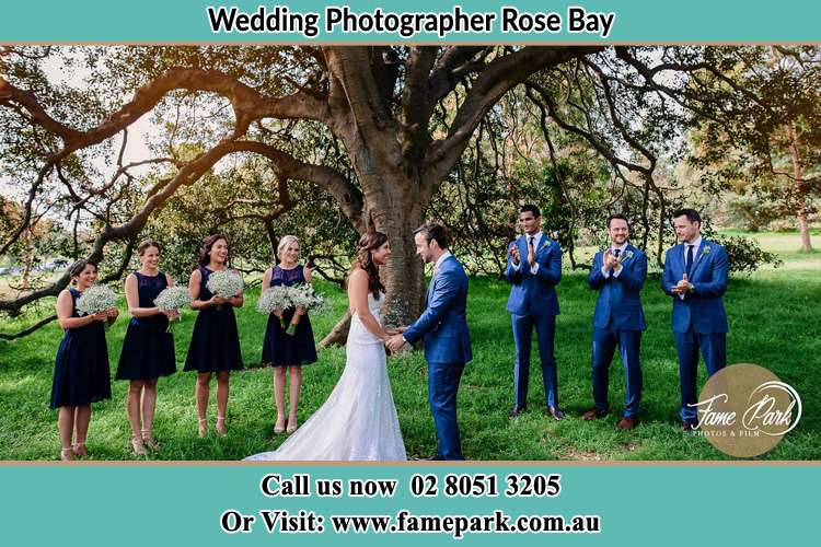 Photo of the Bride and the Groom holding hands with the entourage under the tree Rose Bay NSW 2029