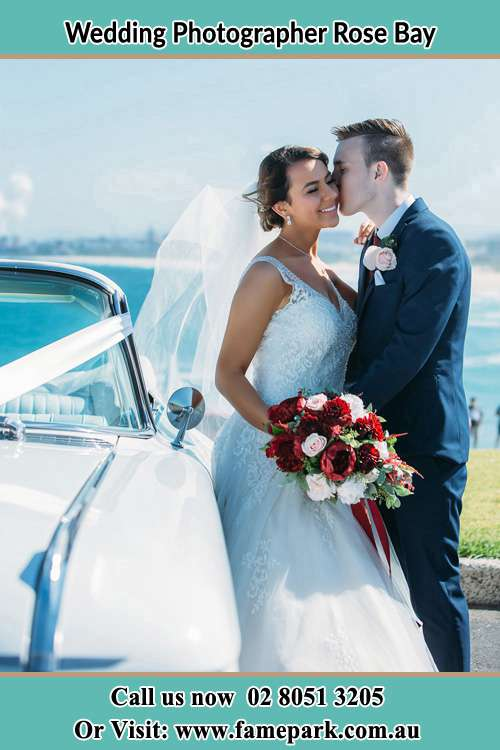 Photo of the Bride kiss by the Groom besides the bridal car Rose Bay NSW 2029