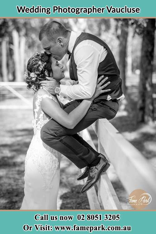 Photo of the Groom sitting at the fence while kissing the Bride on the forehead Vaucluse NSW 2030