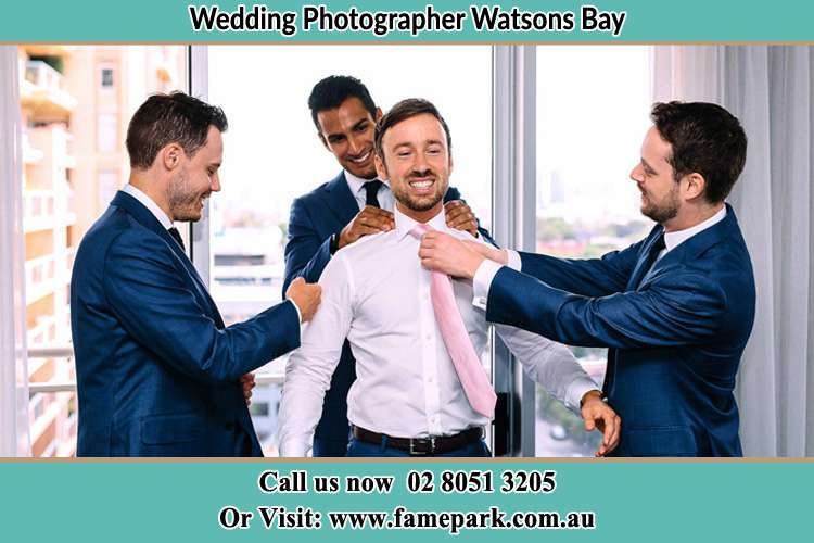 Photo of the Groom helping by the groomsmen getting ready Watsons Bay NSW 2030