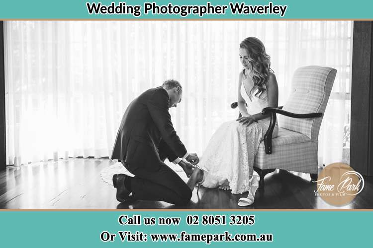 The Bride is being helped by the Groom trying to put on her shoes Waverley NSW 2024